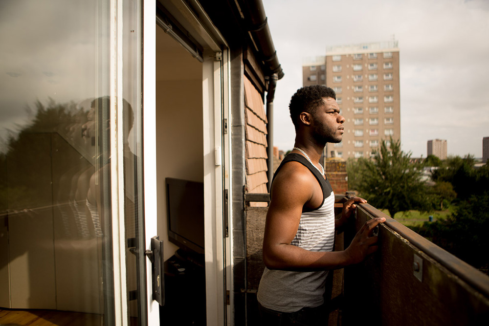 Junior looking out from the balcony of his house,  Erith, 2015  Junior, always looking to secure his future, bought a house with his girlfriend Munjeet when they were both 23 years old; they lived on tins of tuna for 3 months to get the deposit together. Growing up in a council estate, he had never imagined being able to own his own property. Although his house is almost an hour on the train from Hackney, Junior is happy to be surrounded by more trees than concrete. He says his heart will always be in Hackney, he's even on the board of the Shoreditch Trust overseeing community projects in the area, but because of the gentrification, Hackney is not for people like him anymore.
