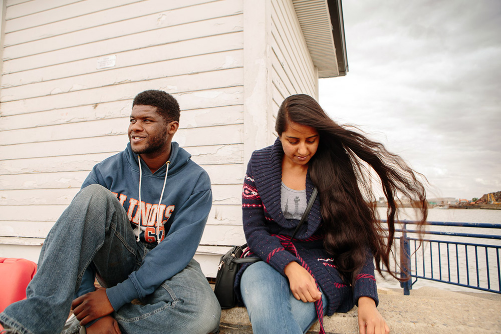 Junior and Munjeet, on the Thames near their house,  Erith, 2015  Junior and Munjeet met at University; three years later they bought a house together. Unfortunately, both of their families could not accept this cross-cultural relationship. They have suffered a sort of exile; Munjeet's parents who are Punjabi, refused to speak to her for 2 years. Luckily Junior's family has come to embrace and love Munjeet, but Munjeet's parents still cannot accept the thought of a black Nigerian son-in-law from Hackney. Munjeet now visits them once a month in an attempt to rebuild bridges.