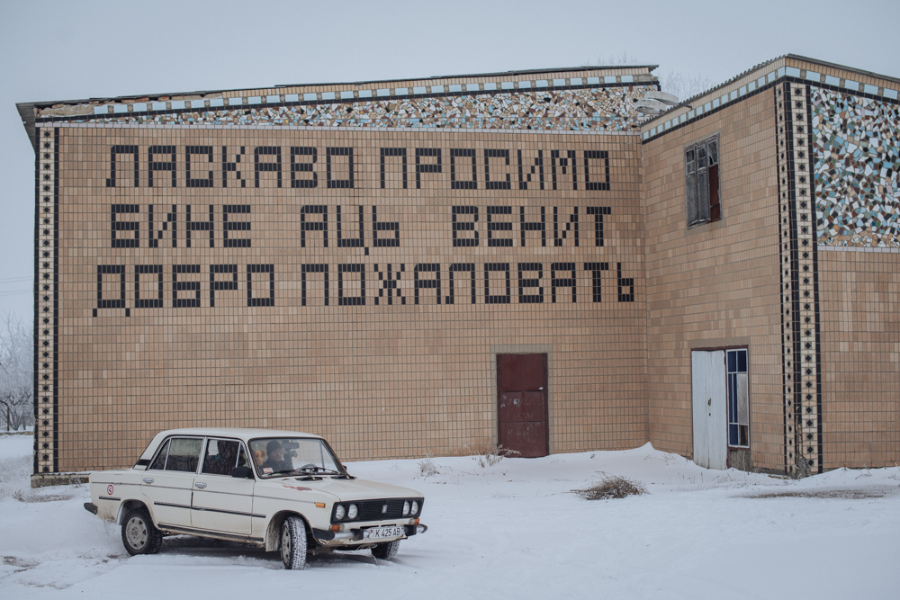 "Many buildings in the villages are reminiscent of the Soviet past, but they are rarely used now. The inscription on the building is the greeting ""Welcome"" in three languages, which are official in Transnistria: Ukrainian, Moldavian and Russian."