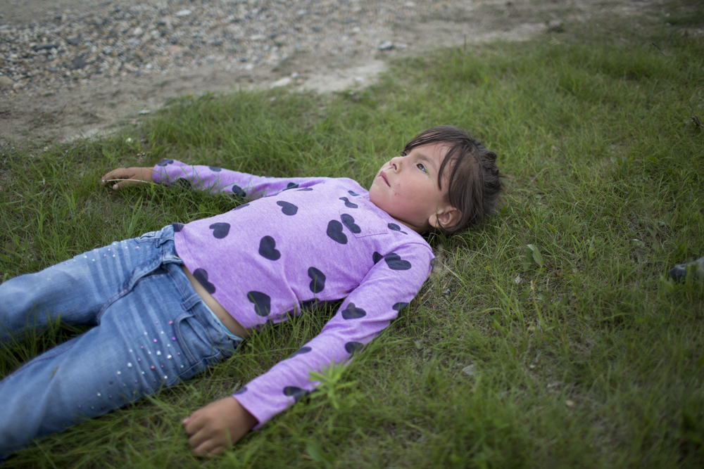 Girl looking up at the sky A young participant lays on the grass outside of Peetabeck Academy following the Fort Albany Awareness Walk.