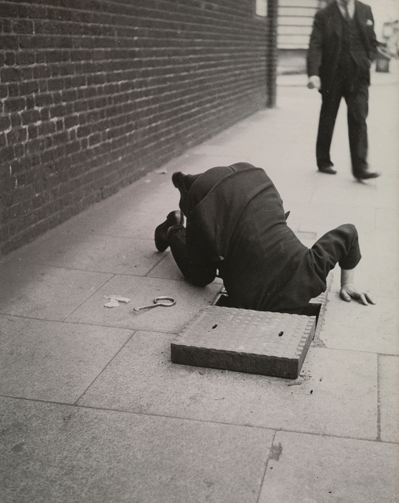 Man with his head in a manhole, London, 1934