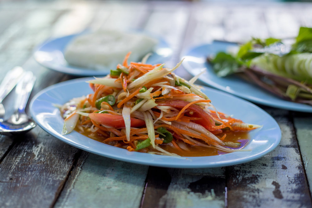 1. Som Tum - Thai Papaya Salad or Som Tum is made from shredded unripe papaya, garlic, lime juice, palm sugar,  lots of green beans, crispy dried shrimp and fish sauce. Sold at every market, always prepared fresh, it costs roughly 25-40 baht and comes with a portion of sticky rice, basil and cucumber. Packs a good punch for a quick power snack.