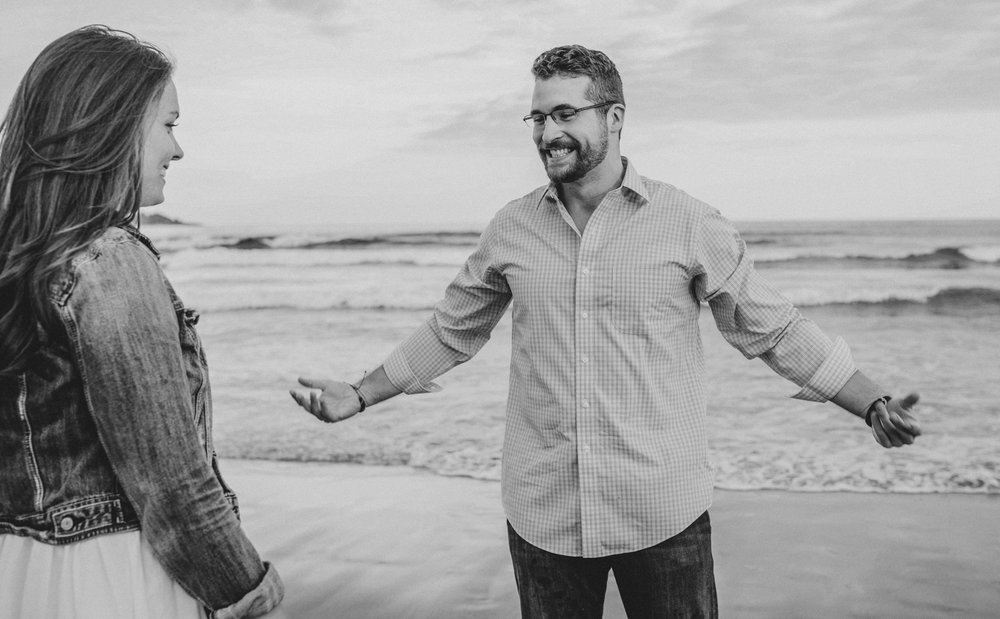couple joking on beach during engagement photos