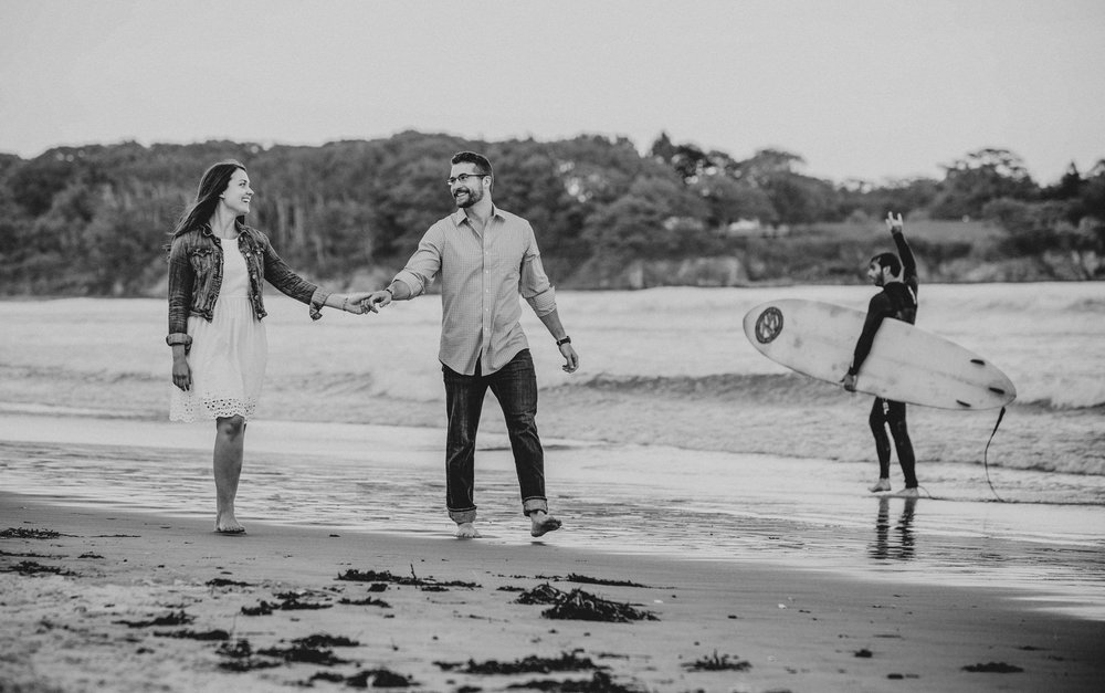 maine engagement photos interrupted by a surfer