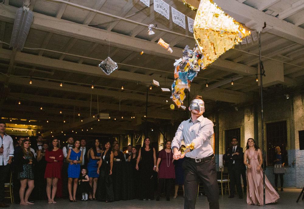 a guest hits a pinata at a maine wedding