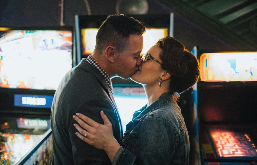 Bride and groom kiss at an arcade in Maine