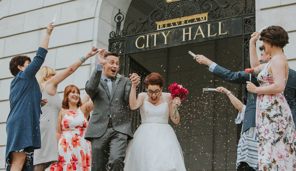 A confetti exit at an elopement at Portland Maine's lovely City Hall building