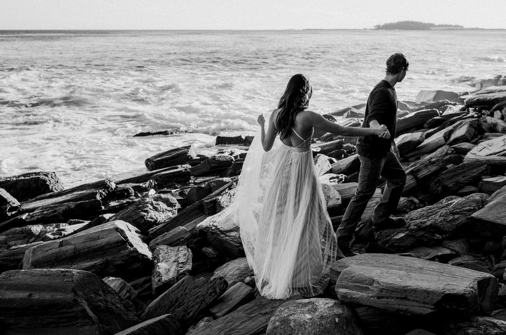 A man leads his girlfriend at their engagement session by the ocean