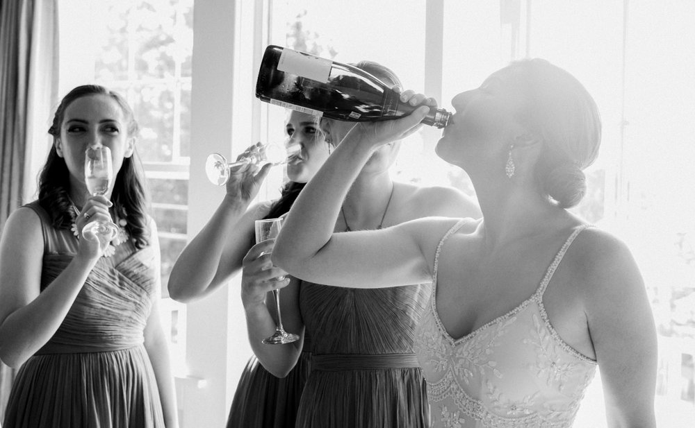 A bride drinks wine before her wedding