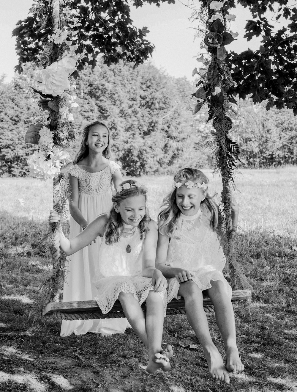 Junior bridesmaids on a floral swing at a Maine wedding