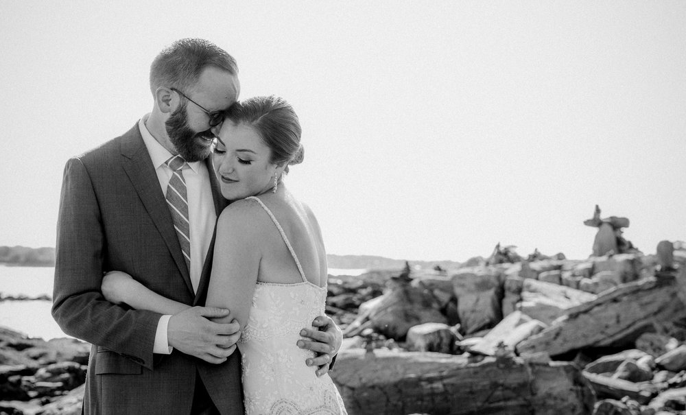 A bride and groom cuddle on Peaks Island