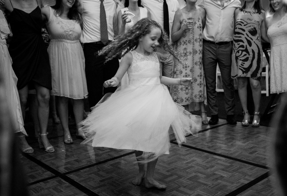 The flower girl twirls at a wedding reception
