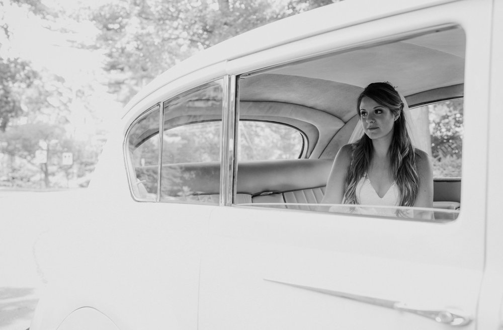 Bride waits patiently on her wedding day in an antique car