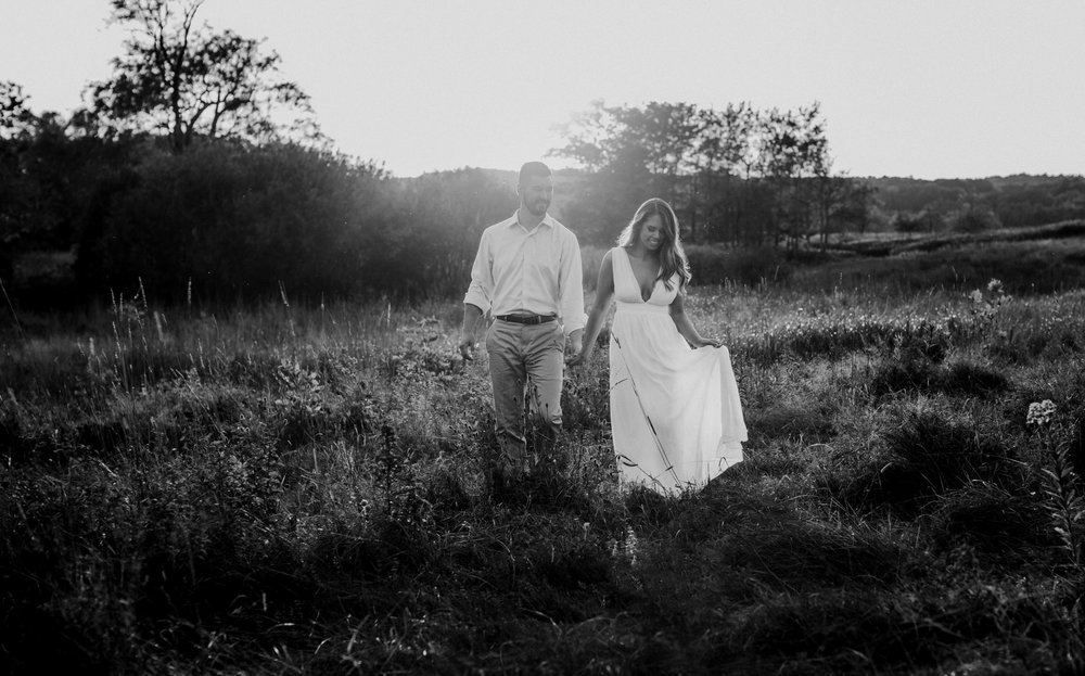 A couple walks in a field