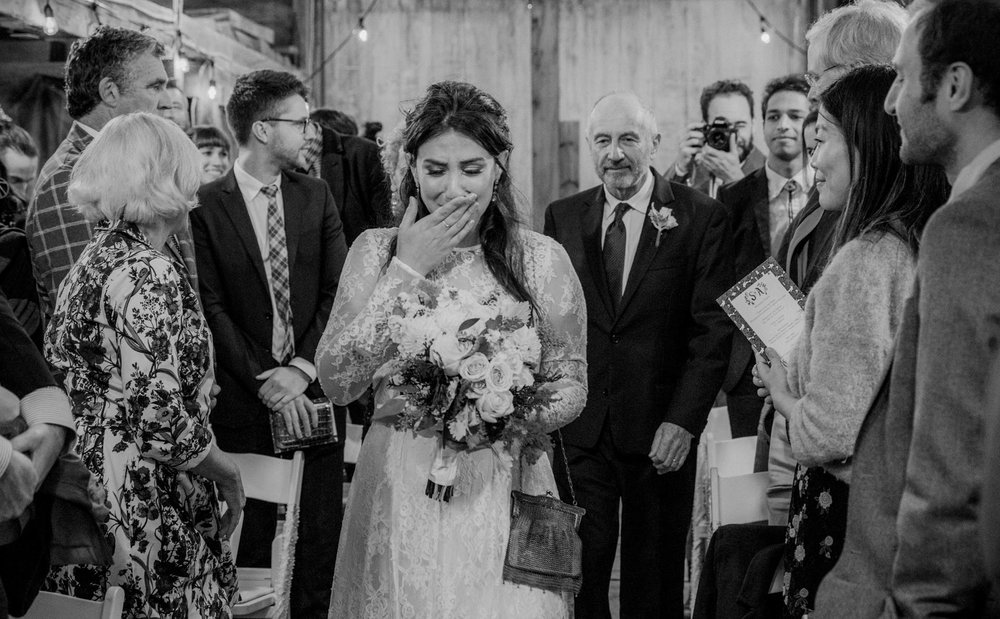 An emotional bride walks down the aisle