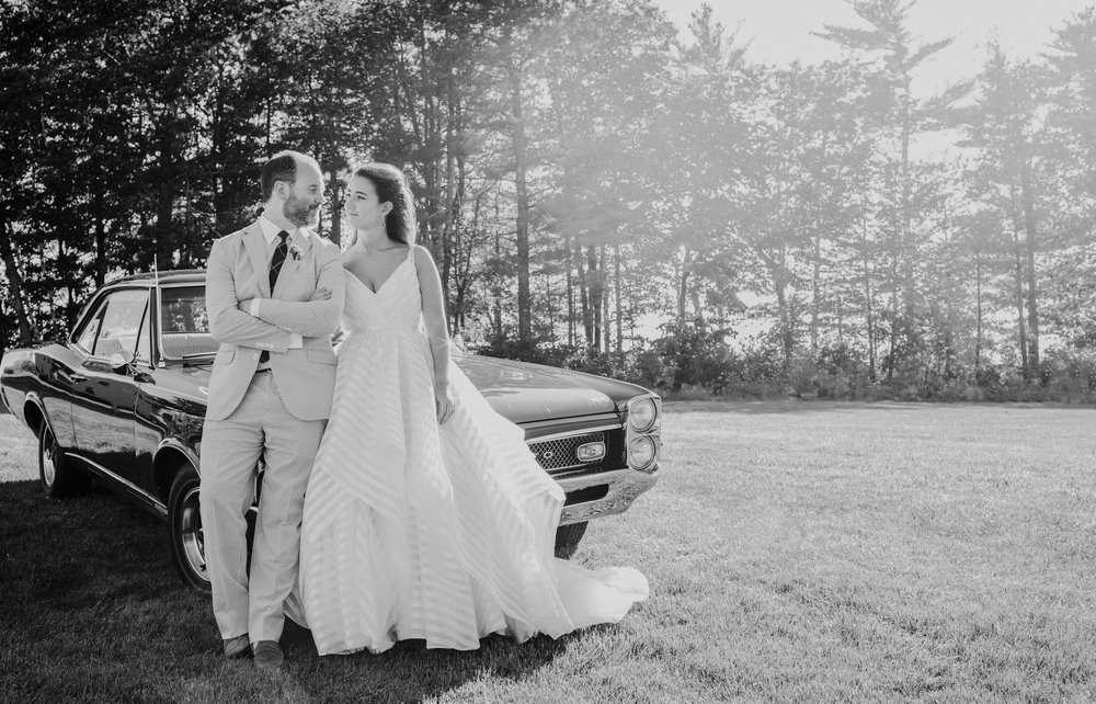 A couple hangs out by their antique car at their wedding reception in Maine
