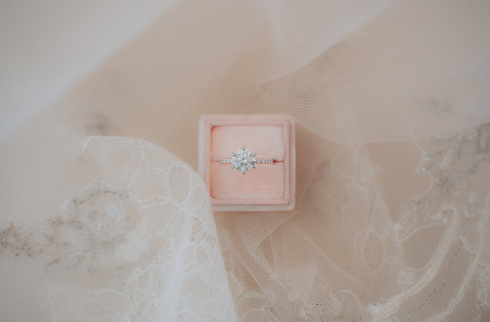 A bride's stunning diamond ring sits in a pink ring box surrounded by her veil