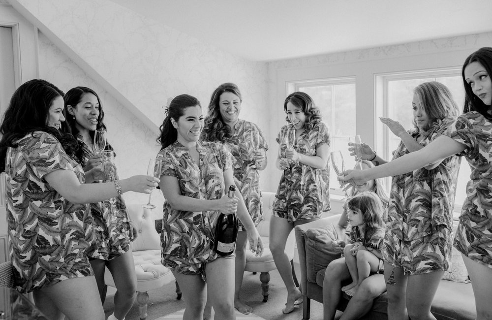 A bride and her bridesmaids crack open a bottle of champaigne on her wedding day