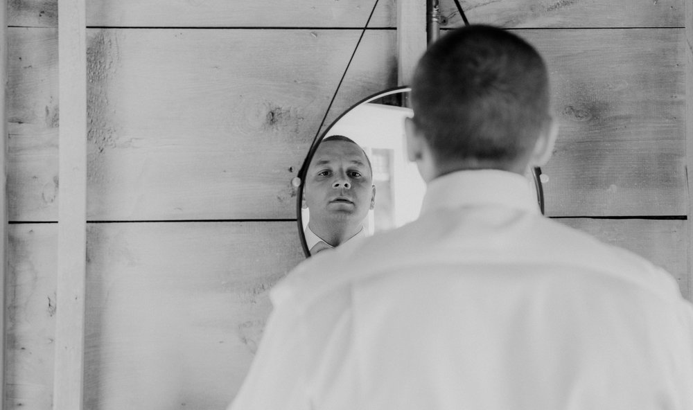 A groom gets ready in a mirror