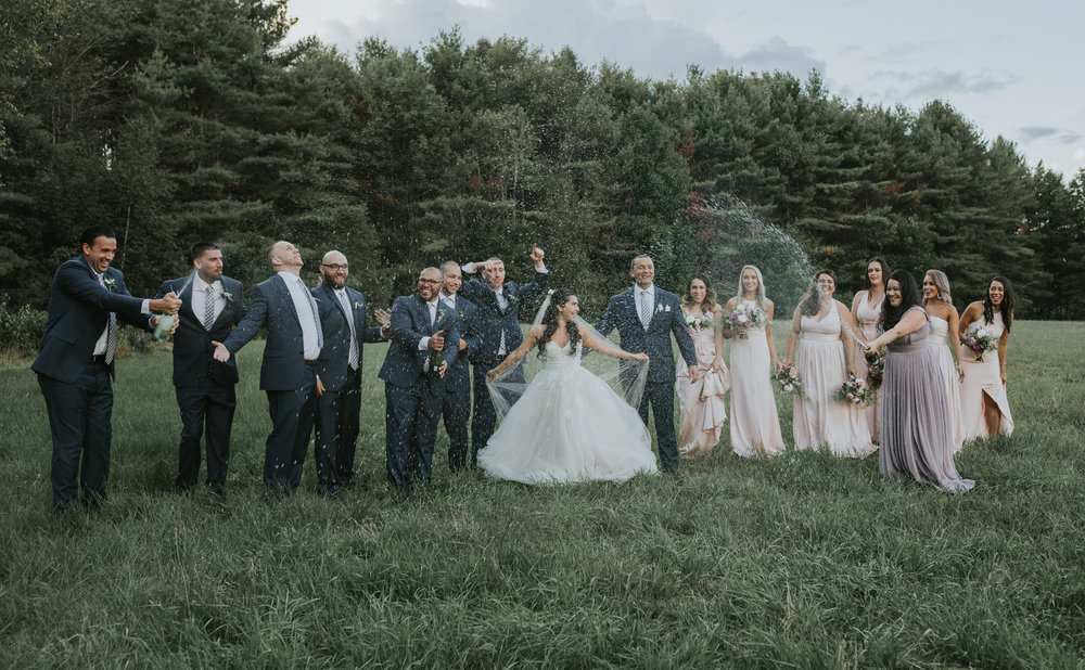 A bridal party cracks open champagne and sprays it everywhere after their wedding
