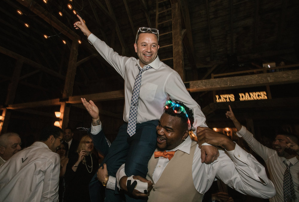 A groom is lifted up at the reception by guests