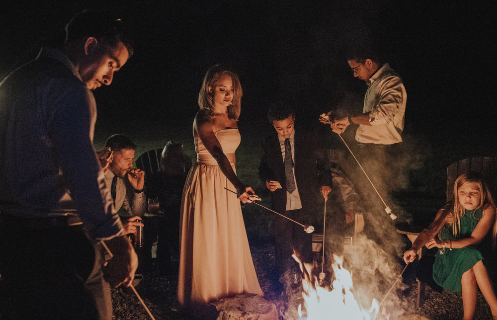 After a wedding the guests enjoy s'mores at a campfire