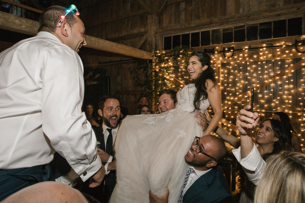 A bride and groom are lifted into the air during their wedding reception