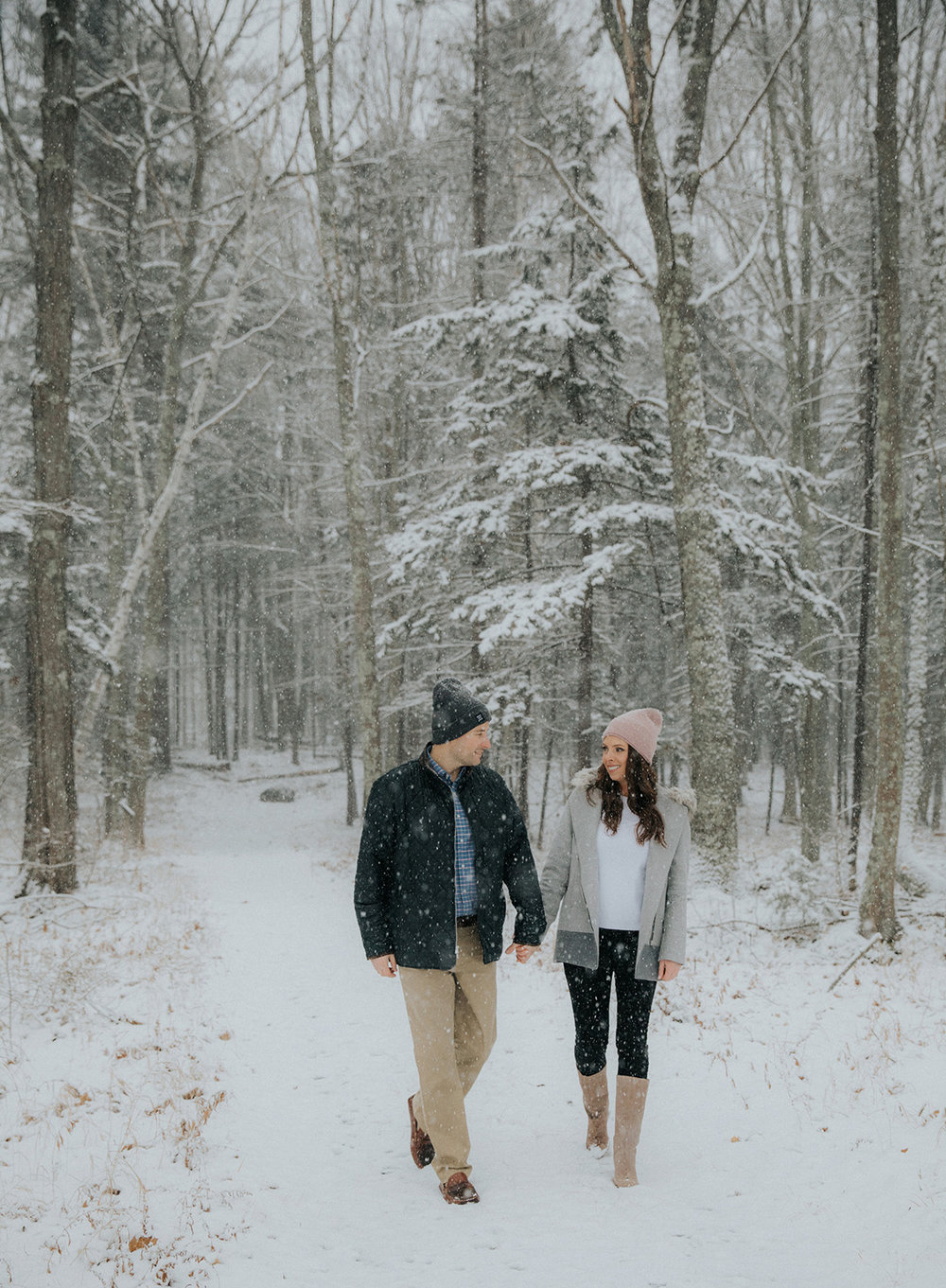A couple walks through the woods in Maine