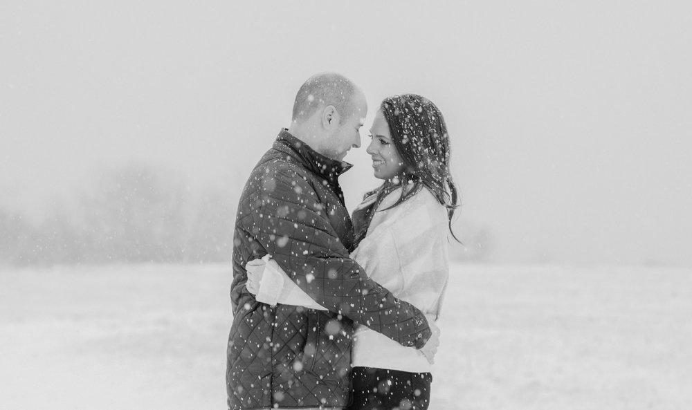 A couple snuggles in the snow