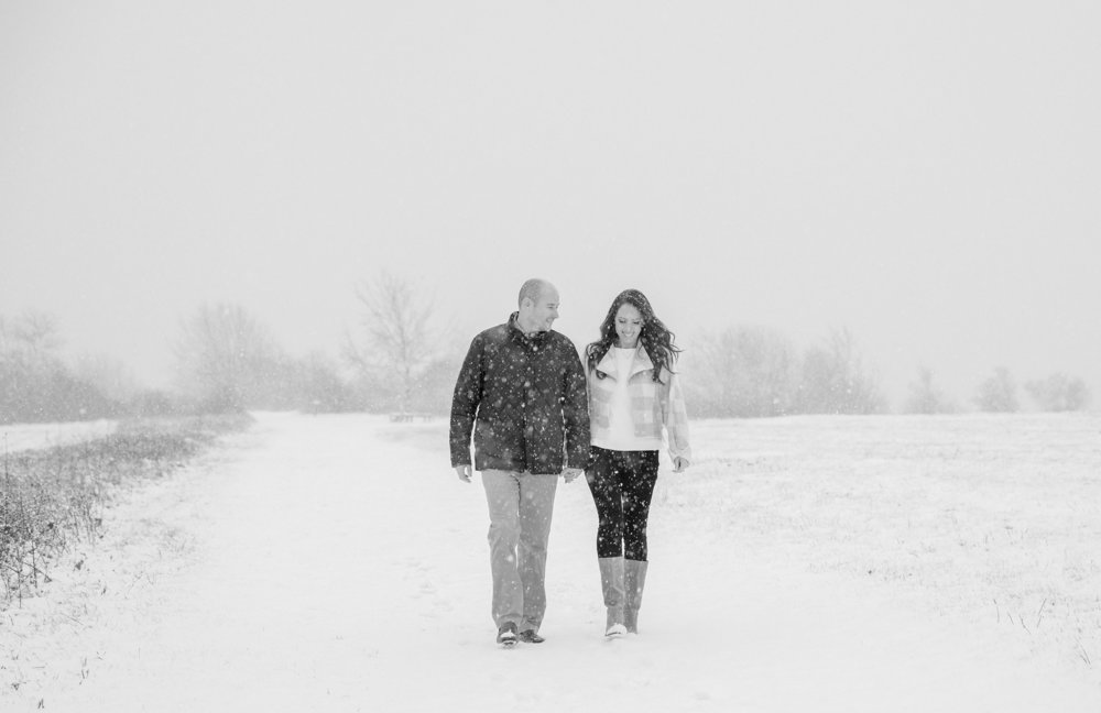 A couple walks hand in hand through a snowy field