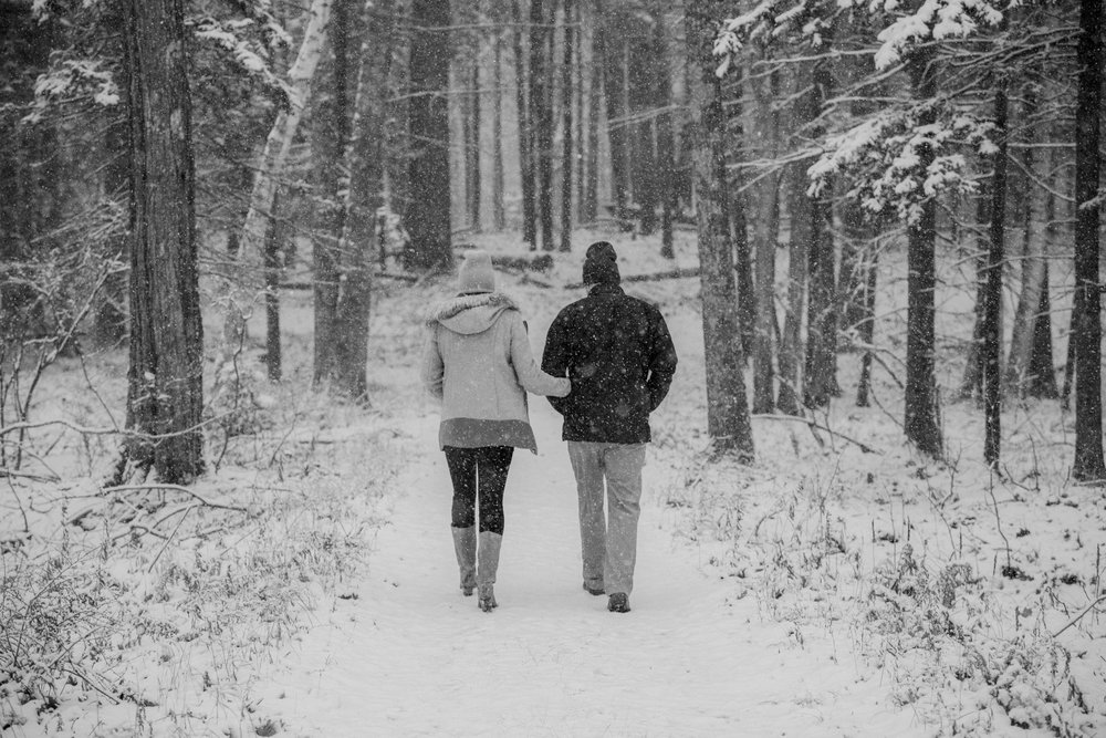 A couple walks in the woods in the snow