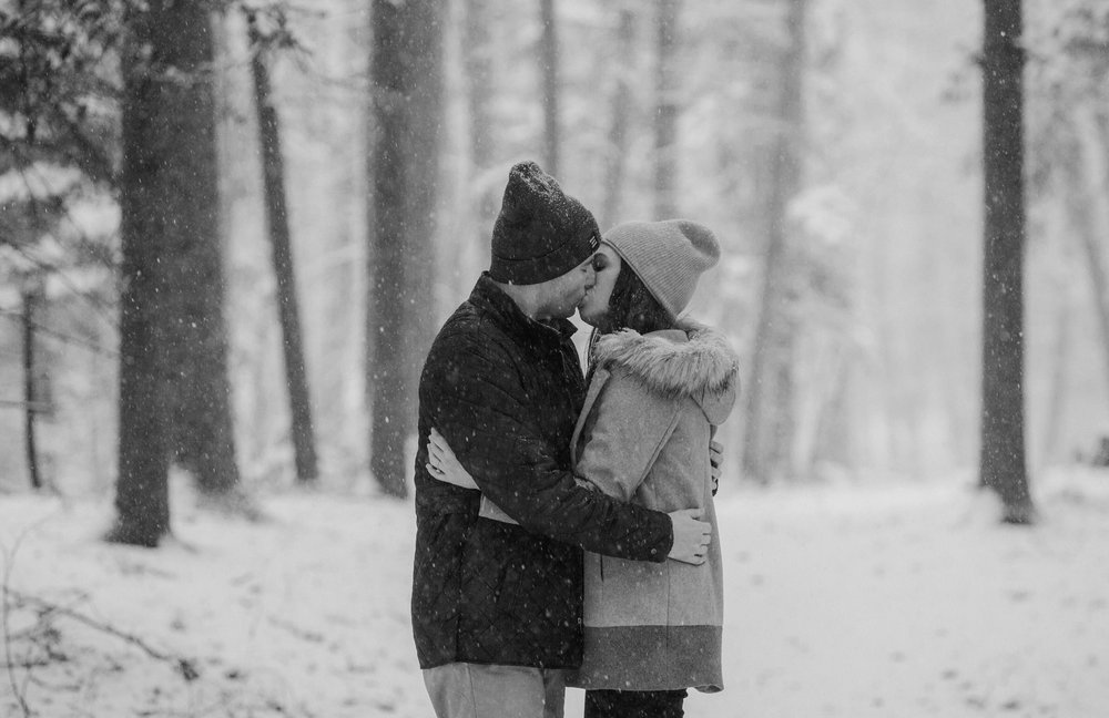 A couple kissing in the snow in the woods