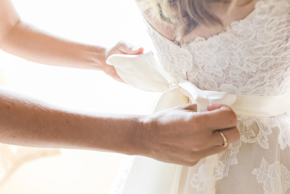 A bridesmaid ties the bow of a bride's dress