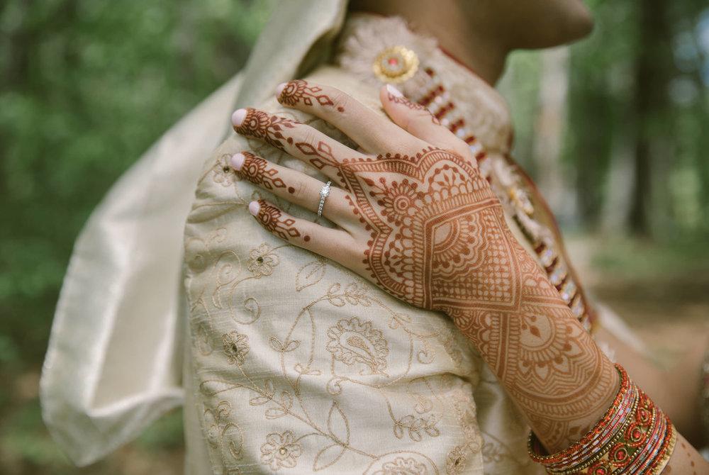 A bride's henna hand on her groom's shoulder