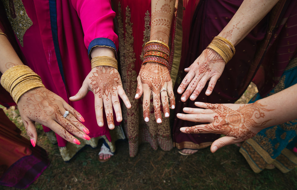 Bride and bridesmaids with henna hands in a circle