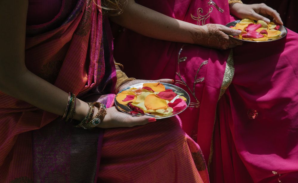 Bridesmaids holding plates of flower petals at an Indian wedding ceremony in Maine