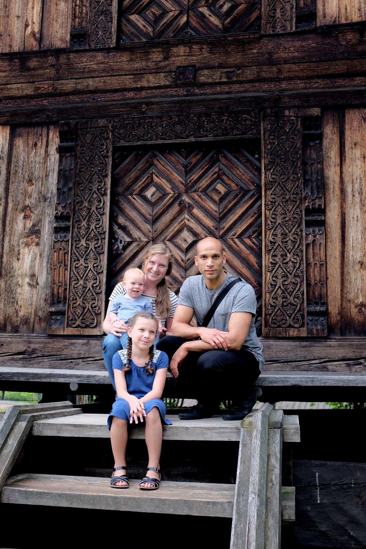 Daniel, Janel & Co posing by a traditional Norwegian house in Oslo.
