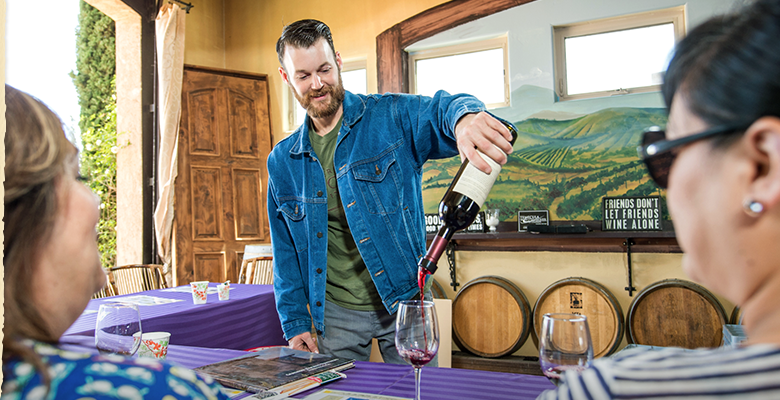 Winemaker Dakota Denton pours a red for guests enjoying a seated tasting.