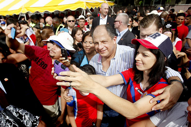 Attendees taking photos with Costa Rican President Luis Guillermo Solis (this image is via: NJ.com)
