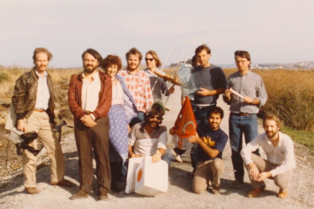 "The ""Mad scientist"" group launching water bottle rockets in about 1986. ""We were launching the rocket for fun,"" Craig said. ""I came back from a visit with Rob Cook at Cal Tech with stories about using liquid nitrogen to blow up pop bottles. Loren Carpenter figured out we could use it to pressurize Alhambra water bottles and the idea took off."" From left, standing: Craig Good*, Loren Carpenter*, Rachel Carpenter, Bruce Young, John Seamons, Mark Leather (someone else hidden behind him), Jeff Mock. From left, kneeling: David Johansen, Neftali Alvarez*, Lane Molpus. *Still at Pixar. © Pixar Animation Studios. All rights reserved."