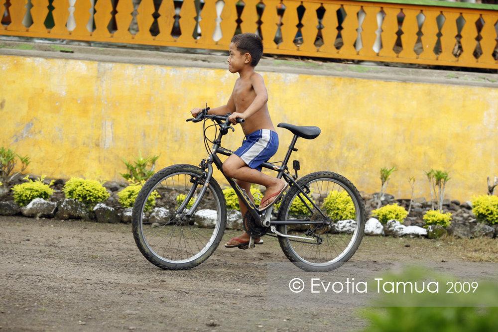 2009 Salelesi, Samoa. Malili Faolua rides past his family faletele (meeting house) on someone else's bike.