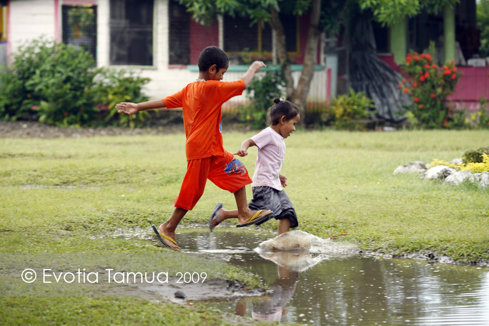 2009 Salelesi, Samoa. Mu Savea and his younger sister Amonia run through puddles in the village malae (green).  Behind them is the Teniteni household.
