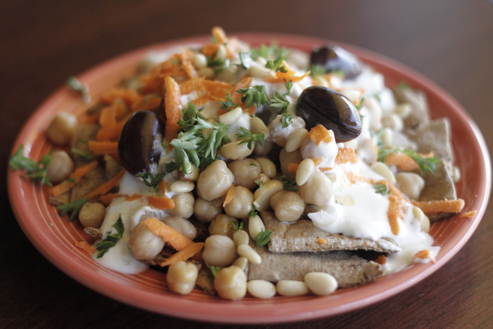 Fatteh     Prepared with whole-wheat Pita bread, yogurt, chickpeas, pine nuts, Tahini paste, olive oil, Kalamata olives, and spices.