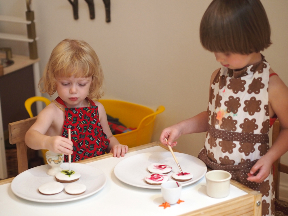 Aoife and Elfie painting biscuits