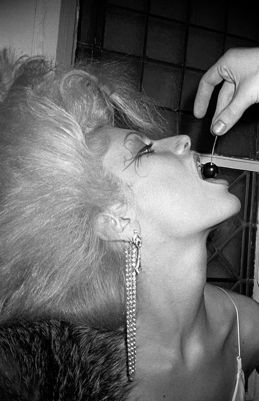 Woman with maraschino cherry. (1985)
