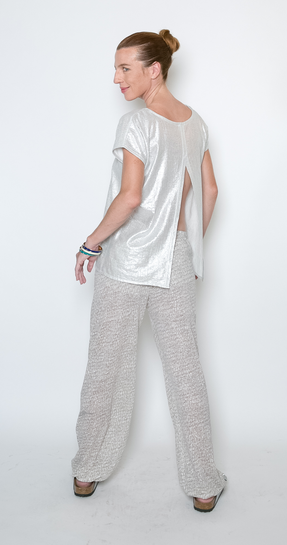 "Sparkle Contemplative Top  #P44P6-26 Sparkle Contemplative Top   $49 #P44P6-32 Sparkle Contemplative Top   $49 Back Button Top, 26"" or 32"" length Silver Sparkle (Rayon/Poly) (Also in Organic Cotton Bamboo solids: Aqua, Black, Navy, Sand, White and Prints) Size XS - XL Gentle Wash Cold, Dry Flat Designed & Sewn in USA   Om Pant      T5583  Organic Cotton Rayon Bamboo     $49 N5583 100% Linen Knit                                   $64 Draped Jogger Pant Self Fabric Cuff   32"" Inseam Sand & Gray Ovals   (Also in solid: Aqua, Black, Navy, Sand, White, Charcoal, Everglade, Fog, Lake, Lipstick, and all Prints)  Size XS - XL Gentle Wash Cold; Hang to Dry   NOTE:  Om Pant was photographed in Aqua Stripes 100% Linen Knit,  production will be 100% Linen Knit AND 55% Organic Cotton/45% Rayon Bamboo Slub from China. The top will still be cut and sewn in USA."