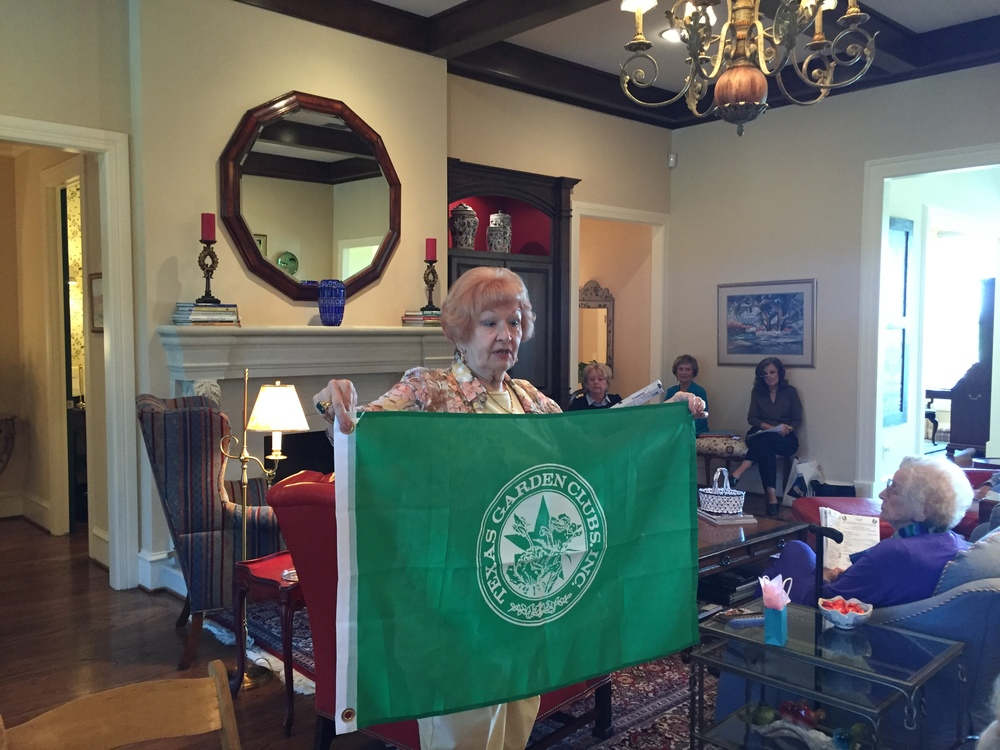 Freda Martin presents a flag she bought and donated to be placed at the Butterfly Garden.