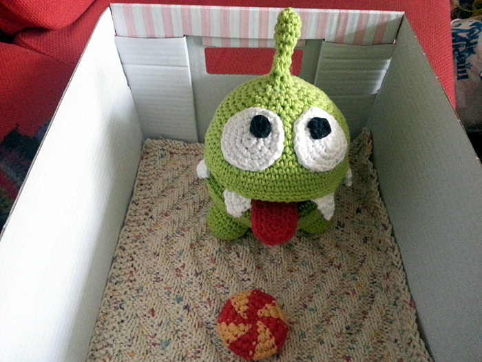 Om Nom with blanket and candy in his box.