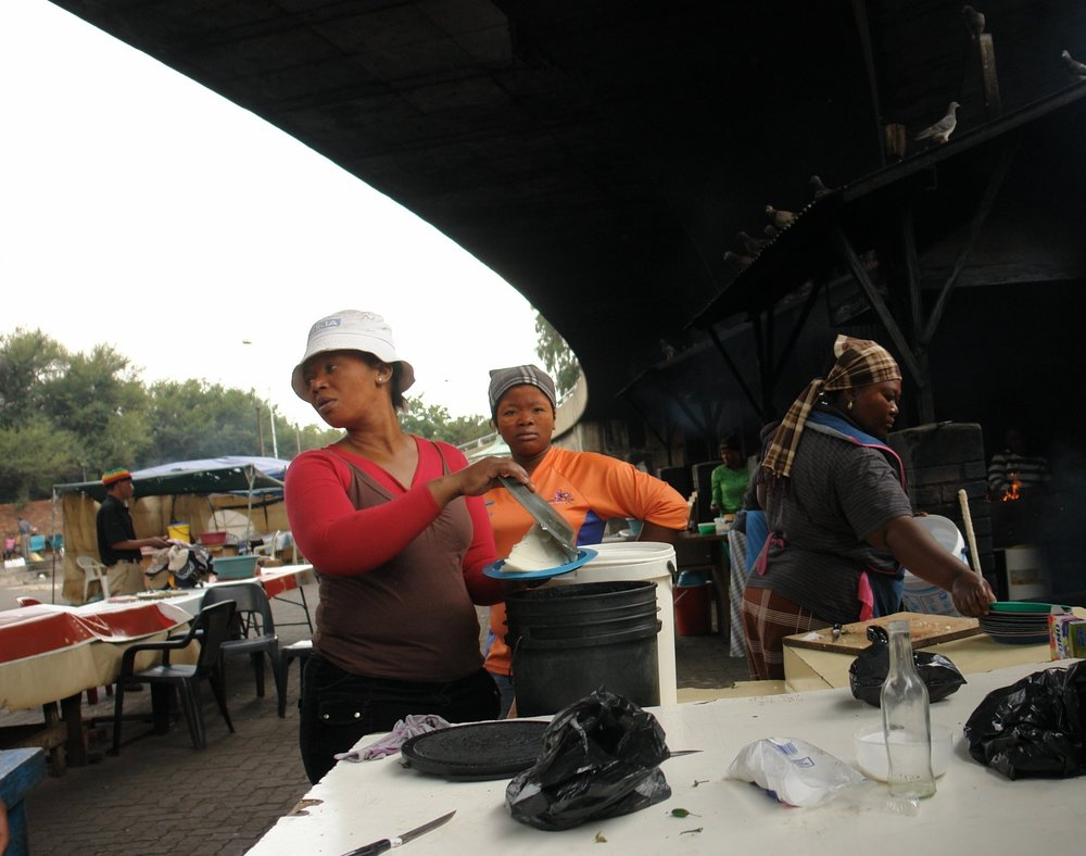 Downtown Johannesburg, Siverwright Avenue, underneath the motorway. At a braai (grill) station a woman serves Phutu Pap (maize and porridge), which is always served with chakalaka (a relish dish) as a side dish with braais.