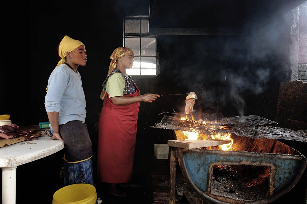 Woman cooking meat on a braai barrel. Downtown Johannesburg
